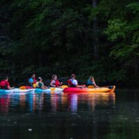 people-on-kayak-boat-near-green-leafed-trees-1497735